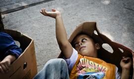 Børnene leger i de tomme papkasser, mens forældrene står i kø efter mad